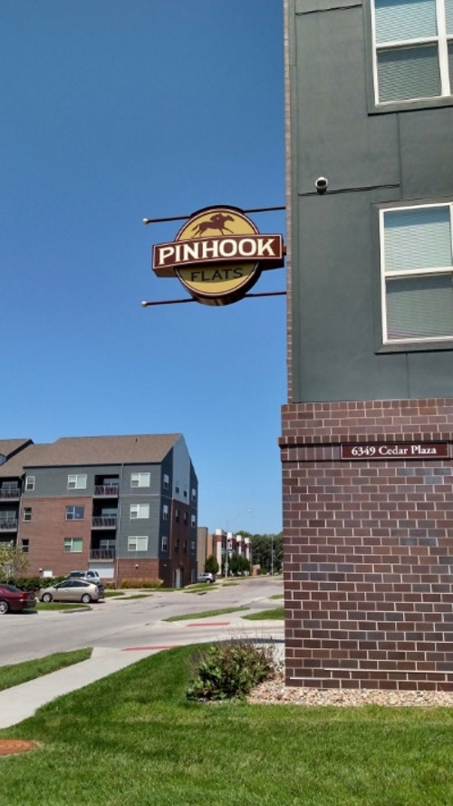 Non-illuminated, double-face projecting sign for Pinhook Flats at Aksarben Village