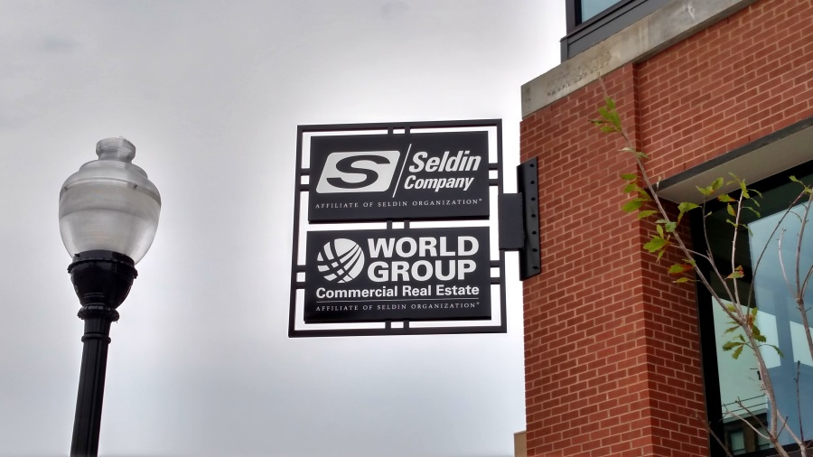 Non-illuminated, double-face Seldin Company and World Group projecting sign located downtown