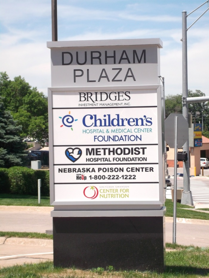 Illuminated, double-face Durham Plaza tenant monument sign at 84th and Dodge